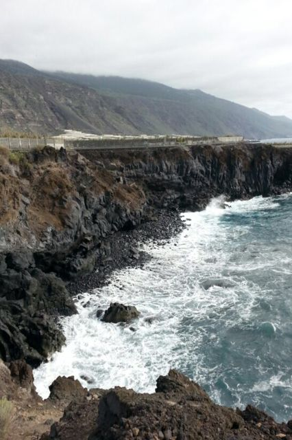 """""""Deze foto heeft mijn vader gemaakt op La Palma, èèn van de Canarische eilanden van Spanje. Ik heb deze foto gekozen omdat ik het een erg mooie foto vind.   Ik zie zee en een soort rotswand, op de achtergrond zie ik nog bergen. Ik denk dat de rotswand nog niet zo oud is omdat het nog erg puntig is, dus nog niet echt versleten door de zee. De bergen lijken me al wel wat ouder omdat ze niet erg scherp meer zijn en ze lijken al wat meer op heuvels.""""   (Vera)"""