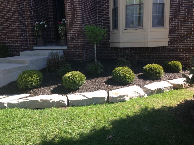Flower bed with natural ledge rock and boxwoods by for Landscaping rocks new plymouth