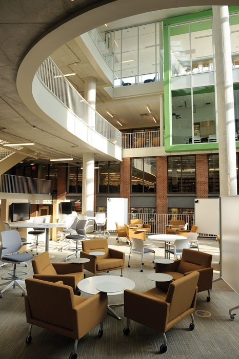 Natural light fills the Schnydman Atrium, where chairs and whiteboards on wheels allow students to adapt the space to their needs. Looking into the room from above are the glass-walled group study rooms.    Brody Learning Commons at Johns Hopkins University.