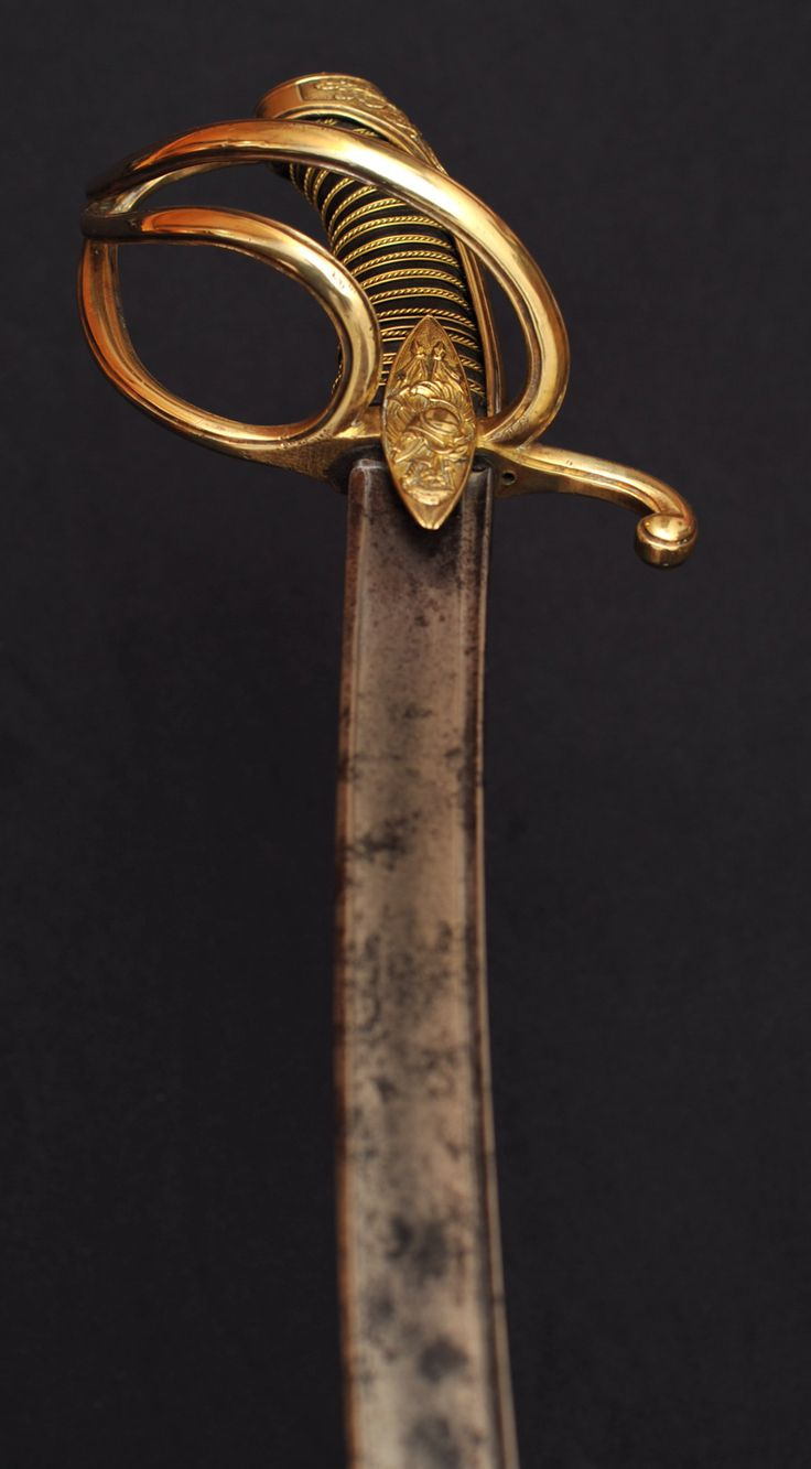 """French Light Cavalry Officer Saber Napoléon Army This a light cavalry officer saber with a """"à la Chasseur"""" hilt from the Napoléon Grand Armée. It has a three branches copper guard with two languets and a long quillon. The two languets feature an Athena helmet and military attributes on one side and oak and olive tree foliages on the other side."""