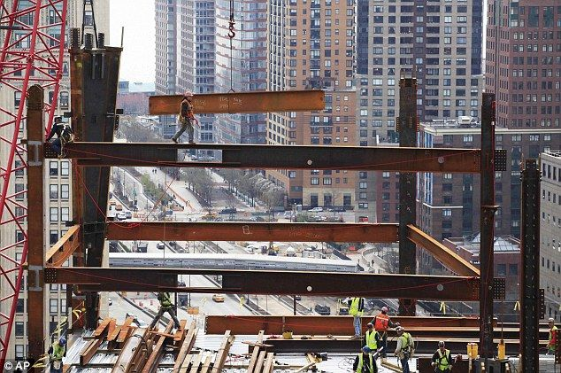 Head for heights: An ironworker, top, walks on a beam as he guides another beam suspended from a crane at the site.