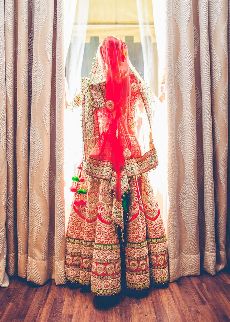 Bridal Lehengas - Red and Green Wedding Lehenga | WedMeGood Red and Gold lehenga with intricate gold and green borders, and gold zari work. Red net dupatta with gold zari border and green latkans. #wedmegood #bridal #lehengas #zari