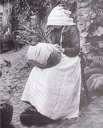 Honiton lacemaker (Devon).  Believed to be Mary Ann Freeman of Otterton, photographed outside her cottage in 1907. She was born in 1843 and had been making lace since she was a young child