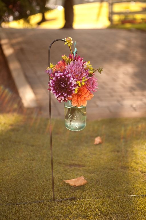 I've got a few (6 or 8) of these shepard hooks and glass containers that we can decorate the entrance with. We could even make paper flowers (or somethnig like that) for inside
