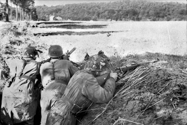 German airborne troops, or Fallschirmjager, shown here manning defensive positions during the early stages of Operation Market Garden, were among the prisoners taken by Allied troops in September 1944. This machine-gun crew appears to be using an American .30-caliber Browning M-1919A4 air-cooled machine gun, probably captured during a previous battle.