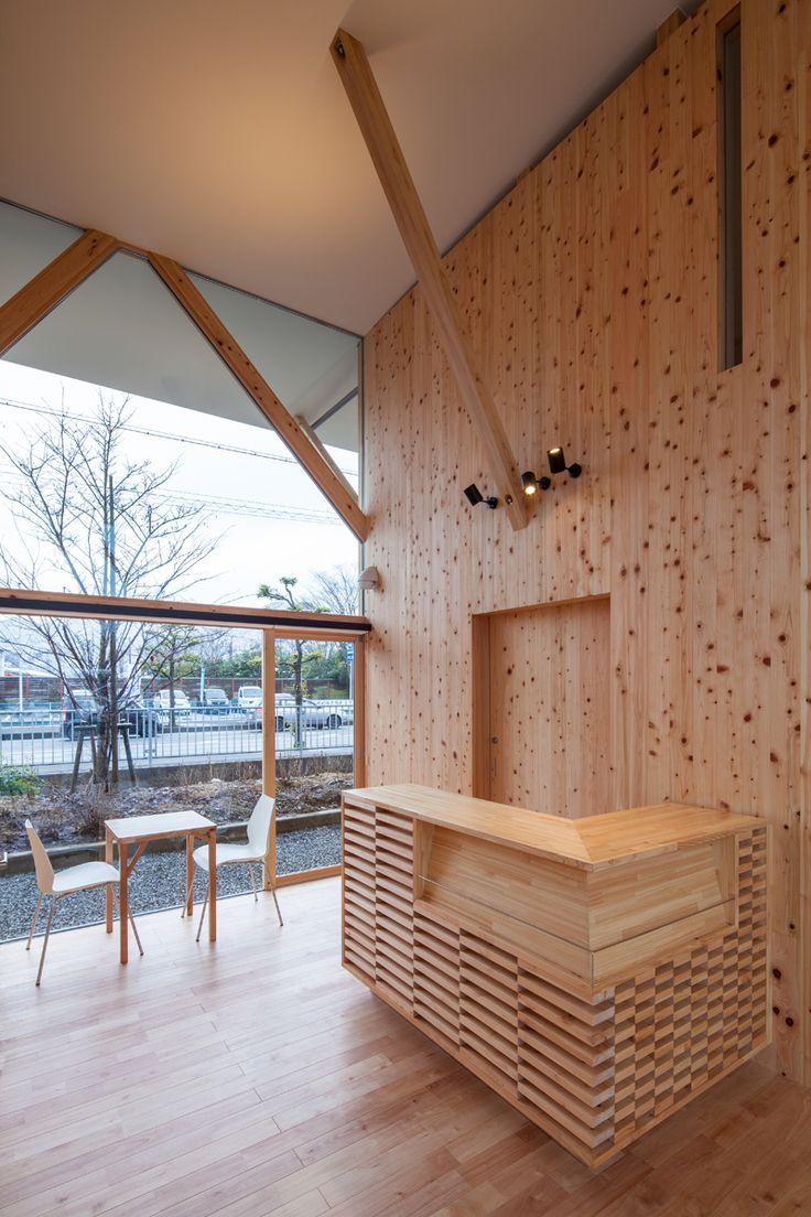 TREE×TREEのインテリア・・・ カウンターは主要な壁仕上と同じ桧材を組み合わせたデザインです。 また、テーブルのデザインは、建物の柱と方杖を縮小した物です。 地場の桧材を使用し、地産地消をコンセプトとしました。 写真:Stirling Elmendorf #事務所#カウンター#カフェ#フラット#大屋根#桧#樹木#外観#シンプル#モダン#住宅#注文住宅#デザイン#ミニマル#家#建築家#設計事務所