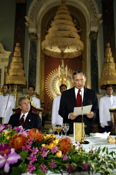 President George W Bush listens as Thai King Bhumipol Adulyadej delivers a speech during the state dinner ceremonies 19 October 2003 at the Grand...