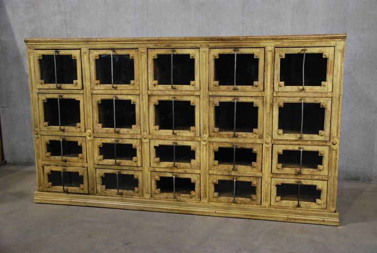 Absolutely one of the best and unique pieces of furniture we have had in  the last while ..This piece is made of pine with decorative details ,glass  fronts , with deep functional drawers. Wine Cellar? Was most likely a store  fixture.  Surface is an aged cracked butter cream color and is all original ..Minor  restoration to base molding.
