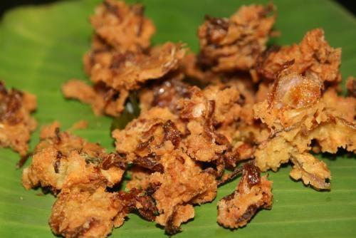 Onion bhaji, beignets d'oignon croustillants  Le onion bhaji (ou bhajee, l'orthographe varie) : beignets d'oignons croustillants avec des petits morceaux de piments (doux) dedans. Délicieux ! Servis ici sur une très esthétique et très verte feuille de bananier (ce qui veut dire qu'on est dans le Sud de l'Inde).
