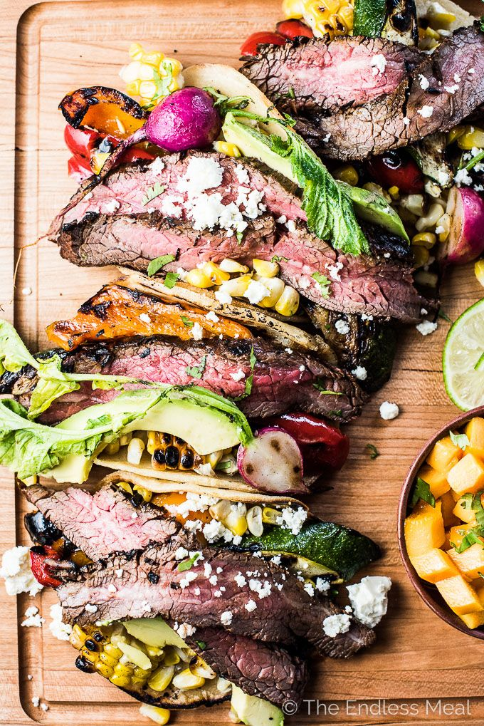 These CRAZY delicious Grilled Steak Tacos are the ultimate summer BBQ recipe. Inspired by Mexican carne asada, the steak is marinated till flavorful and tender then grilled over high heat so the outside is charred and the inside remains pink. The tacos are piled high with steak and grilled summer veggies for an easy to make and healthy dinner recipe that everyone will love. | theendlessmeal.com