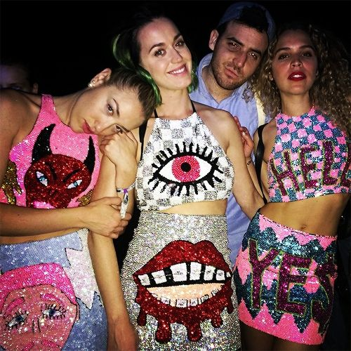 """Here's Katy Perry with her girls chilling at Coachella. Their tops: A devil head, an all-seeing eye and """"hell"""". It's like an Illuminati for kids fashion show."""