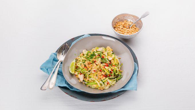 Veel noedels, maar weinig koolhydraten? Dat kan. Maak de noedels van courgettes voor een koolhydraatarm gerecht. Peper snijdenSnijd het steeltje van 1 rode peper. Halveer de peper in de lengte en verwijder met een scherp mesje de zaadlijsten. Snijd het vruchtvlees fijn en 2 tenen knoflook fijn. Kipfilet meebakkenVerhit 1 eetlepel rijstolie in een ruime hapjespan en fruit de helft van de knoflook en de helft van de rode peper. Voeg 300 gram kipfiletblokjes toe en bak 4 minuten mee. Raspen met…