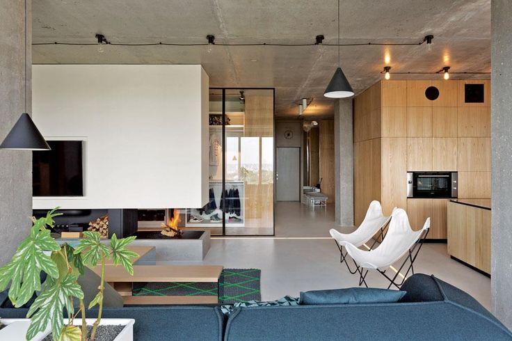 Transición de una cocina comedor integrada con el living. Sofás gris topo, una dupla de sillas BKF, mesa baja de madera y columna central que aloja el televisor y divide parcialmente el living del vestidor contiguo.