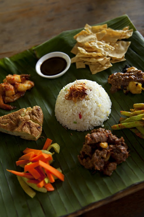 Malaysian feast with various condiments on a fresh banana leaf
