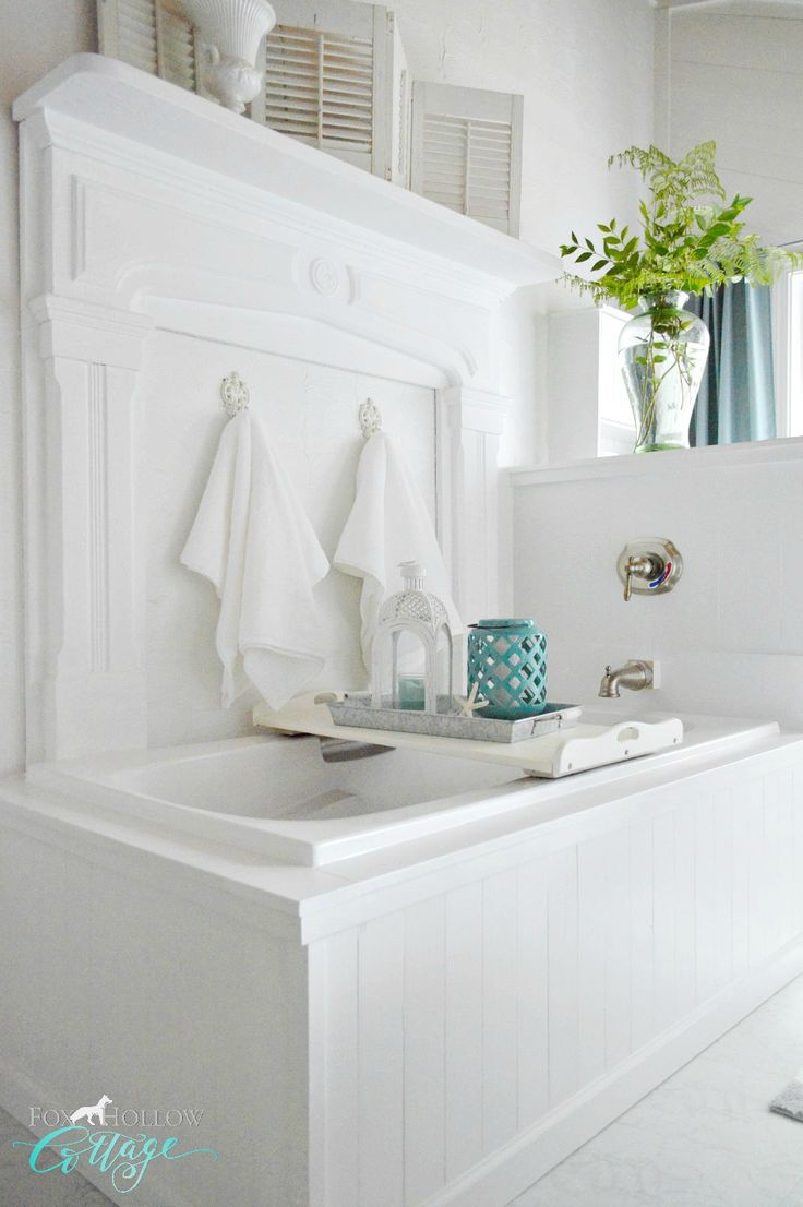 No budget to remodel? Paint it. The white wood wrap around tub surround offers a cottage feel to this coastal inspired bathroom. The mantel adds character and a unique twist! The tub, seldom used, was painted white to hide the dingy vanilla color!