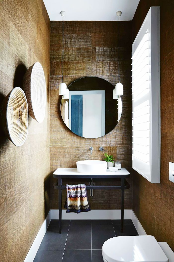 Chic, black tiles, a large mirror, and textured, brown walls add dimension to this small bathroom.