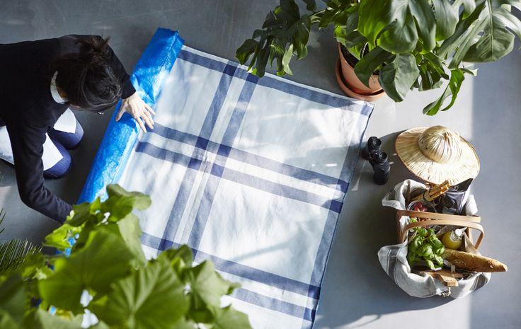 Femme en train de rouler une couverture de pique-nique réalisée avec des sacs bleus IKEA et des torchons de cuisine