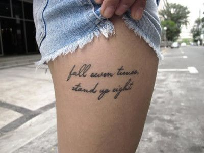 "thigh tattoos for girls with the quote ""Fall seven times, Stand up eight"" written on the outer thigh."