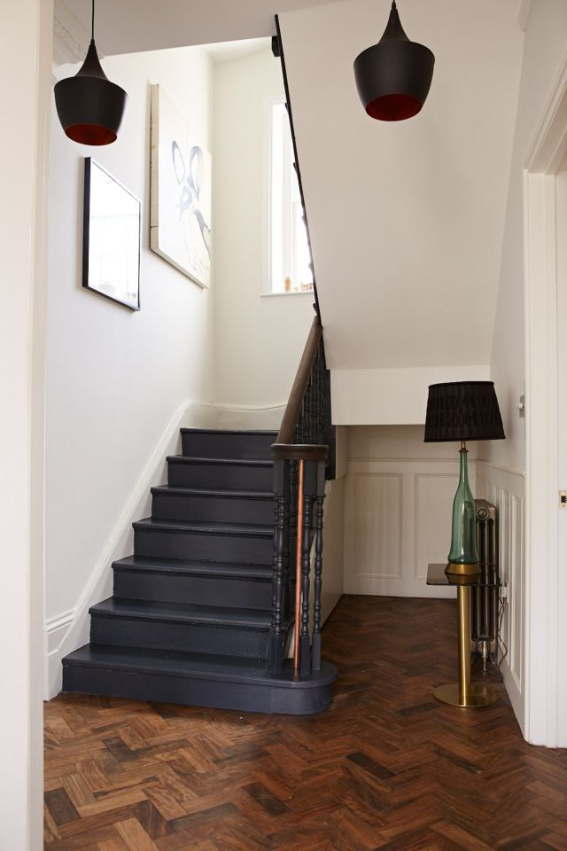 Dark blue painted wooden stairs and herringbone floor.