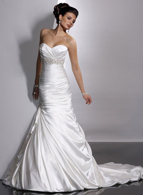Adorae Bridal Gown by Sottero and Midgley: Fit and flare gown with sweetheart neckline and available with zipper or corset closure. Demir Stretch Satin provides sleek luster to this slender silhouette. Ruching envelopes the bodice and asymmetrically plummets below the waist, while the train pours into a gorgeous balloon hem.