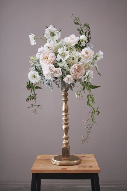 Beautiful DIY tall centerpiece made with spray painted wooden candleholders or premade table leg screwed to a wooden base. Attach a plastic floral bowl and voila! WOW so chic!