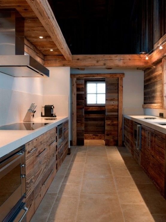 The rustic look of the wood cabinets is simply perfect with the white countertops.