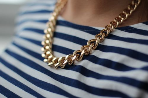 Gold chain on nautical stripes.