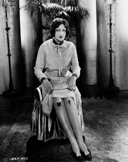 Joan Crawford ~ modeling a new pair of tights aimed to show men what you think of them. If you're unimpressed you show them the left knee with the icicle on it. If you like them, you show the right knee with the heart. @Sock Dreams you might be interested in this.