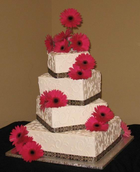 Pink Gerbera Daisies highlight this 4-tier asymmetrically stacked wedding cake. Ribbon embellishes the bottom borders while white scrolls on white buttercream icing add texture and beauty.