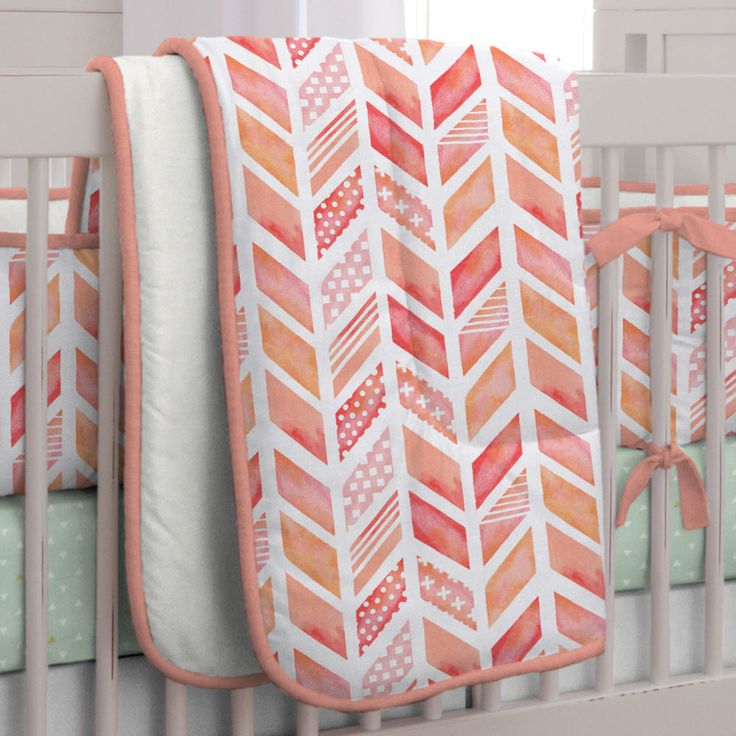 """Nursery Coverlet in Coral Watercolor Herringbone by Carousel Designs. Lullaby and goodnight! Our soft and cozy box-quilted comforter will keep your baby toasty warm on a chilly night, and makes for a great tummy-time mat by day. Measures approximately 36"""" wide by 46"""" long. Our crib comforter batting is made from recyclable hypoallergenic polyester fiberfill."""