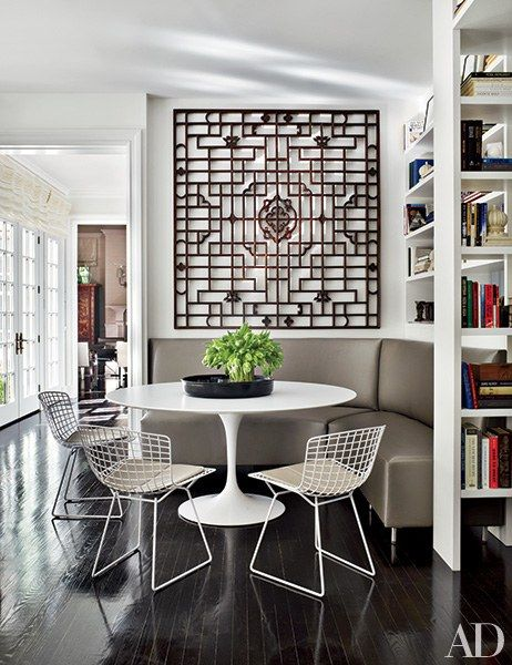 In the breakfast area of a Westchester County, New York, home devised by designer Vicente Wolf, an antique Chinese screen presides over a banquette and dining table. | archdigest.com