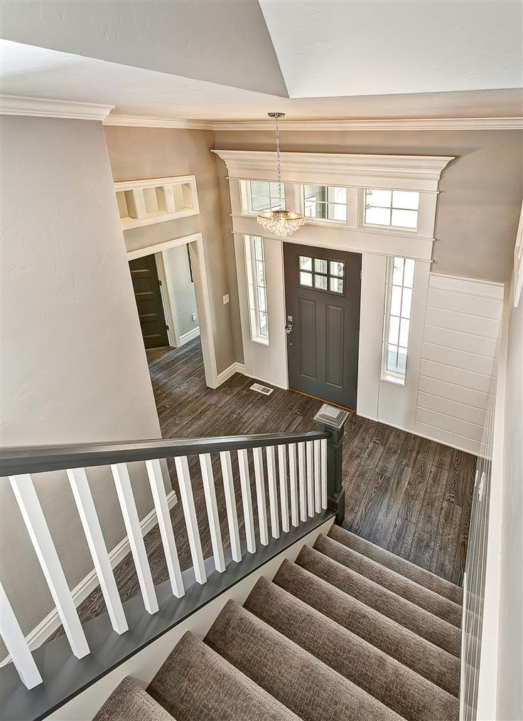 Stunning: Entryway with gray stair rail and white ballusters. Crystal entry chandelier. Tuftex carpet with Manningtons Restoration Collection laminate flooring in Black Forest Oak fumed. Benjamin Moore Kendal Charcoal front door with White Dove trim. Transom windows above door frames.