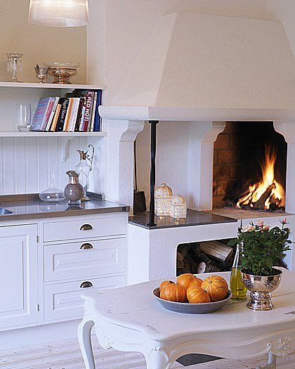 Clean white everywhere paired with gray accents and an open fireplace (could you make pizza on that?)