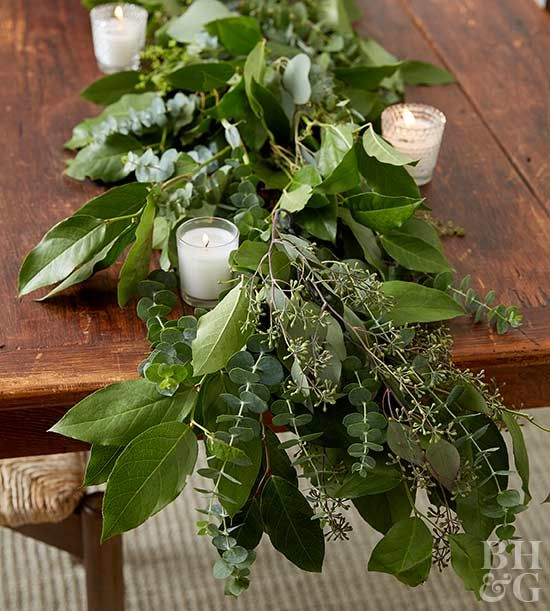 Create a stunning Christmas table decoration using bundles of holiday greenery.