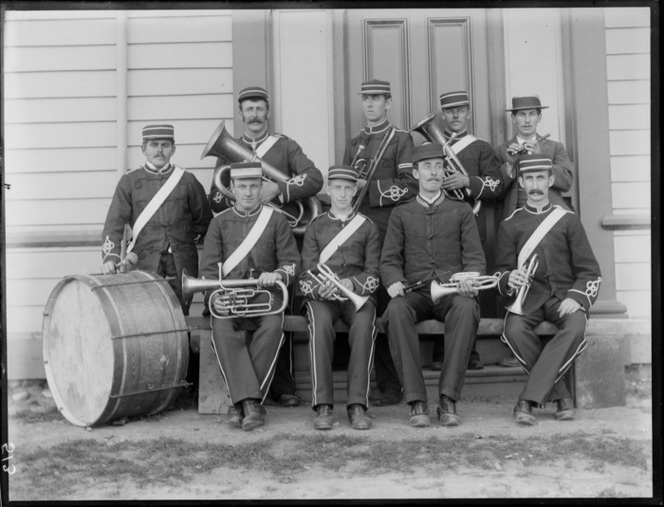 Members of a brass band, in uniform, next to building, probably Christchurch district