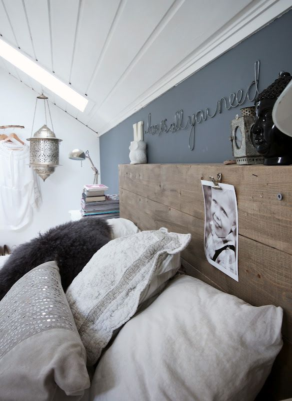 Neutral bohemian attic bedroom with shades of grey, painted wood paneled ceiling, skylight, and lantern.