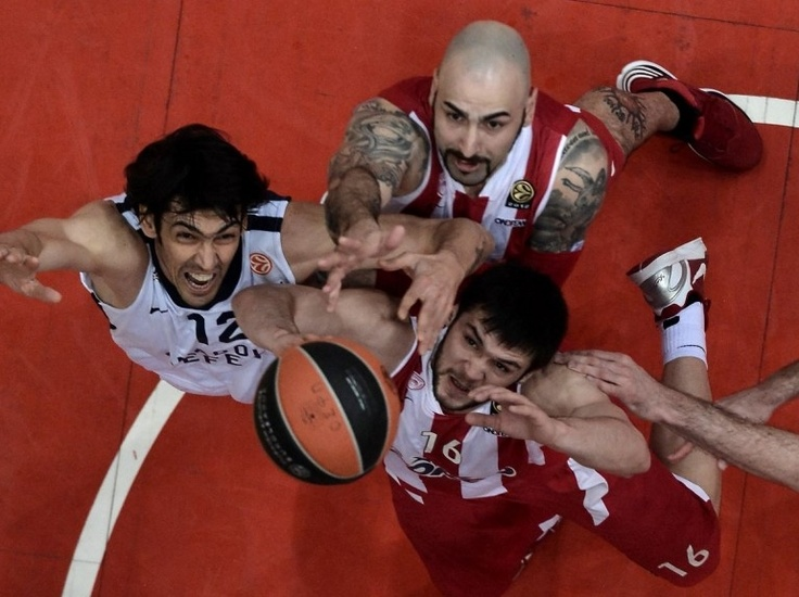 Kostas Papanikolaou (en bas à droite) et Pero Antic, du club grec de l'Olympiakos, à la lutte avec Kerem Gonlum, du club stambouliote Anadolu Efes, lors d'un match d'Euroligue à Athènes, le 10 avril. (AFP PHOTO / ARIS MESSINIS)