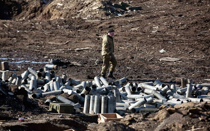 A fighter with the Donetsk People's Republic army looks for ammunition in a destroyed Ukrainian army compound in the town of Debaltseve