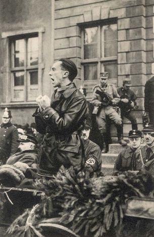 Berlin, Germany, The Nazi Minister of Propaganda Josef Goebbels speaking in a street. Goebbels was responsible for controlling the German news media, literature, visual arts, filmmaking, theatre, music, and broadcasting. As the central office of Nazi propaganda, the Reichs Ministry of Public Enlightenment and Propaganda comprehensively supervised and regulated the culture and mass media of Nazi Germany.