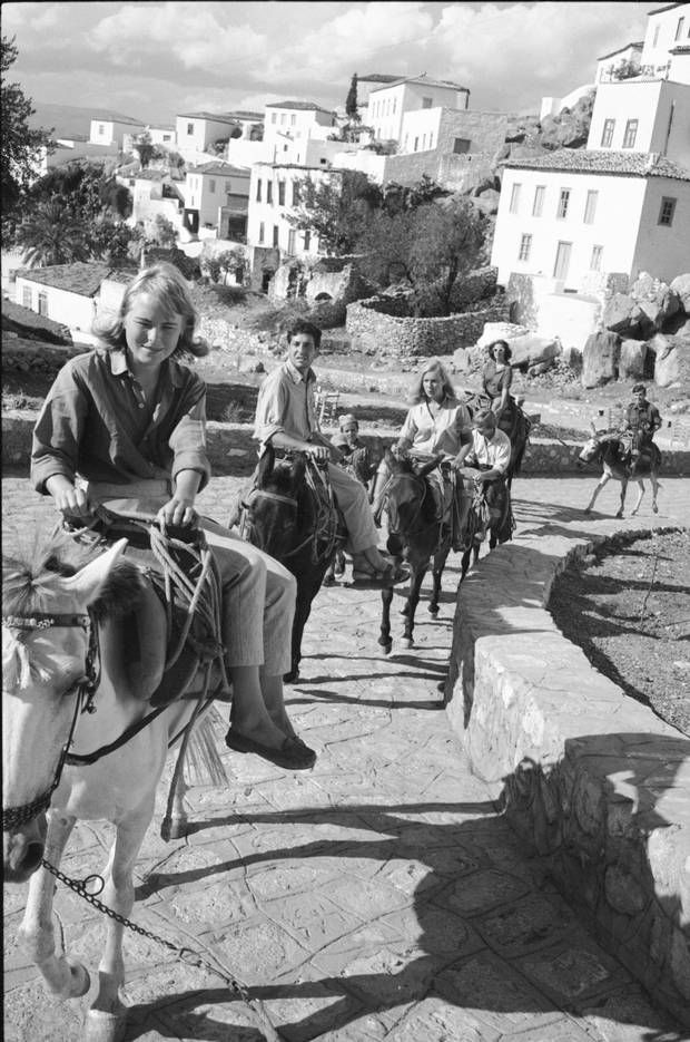 Marianne Ihlen, Cohen and friends ride mules along a stone path on Hydra…