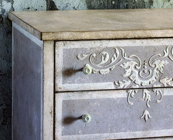 Pretty. stucco stencil. Could also be done with the wooden embellishments used for fireplaces found at Lowe's and Home Depot. They could easily be prepainted in a different color from the piece itself.