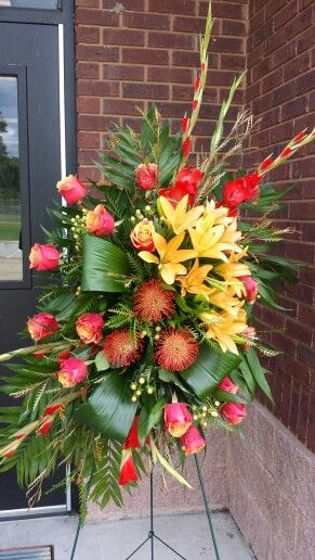 Red and Orange standing funeral sympathy spray with roses, protea, lilies, and gladiolas