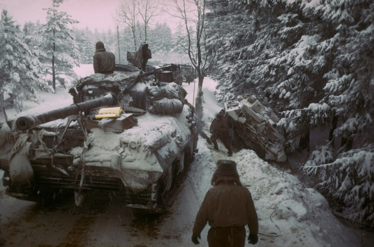 An American tank moves past another gun carriage which slid off an icy road in the Ardennes Forest, 1945