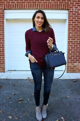 The versatility of a dark red knit oversized sweater and navy blue slim jeans makes them investment-worthy pieces. For footwear go down the classic route with grey suede booties.