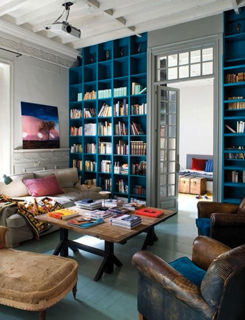 bright turqoise blue cube built-in bookcases, massively high ceilings, decorative victorian plaster, bright white walls and rooms, painted blue hardwood floors, french doors with awesome transom window, old leather chairs...and dont let the painted library ladder on the right pass you by-it matches the book shelves... this house seems pretty awesome