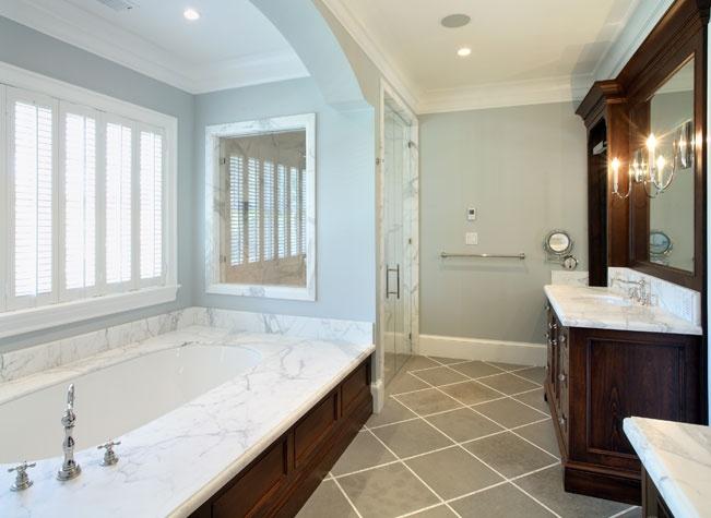 Grey tiled floor.  Marble shower.  Dark wood details.--girls' bath?