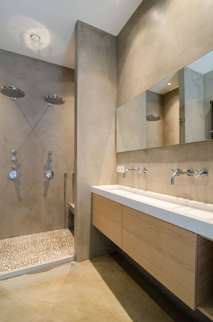 Adjacent to the bedroom, the bathroom features microcement-coated walls, along with a custom sink and vanity. Dornbracht Tara sink faucets and dual rainfall showerheads finish the space.