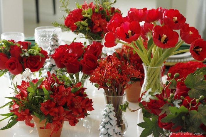 mix de flores e arranjos vermelhos para mesa de natal. Rosas, cravos e tulipas vermelhas em diferentes alturas ajudam a enfeitar o centro de mesa.