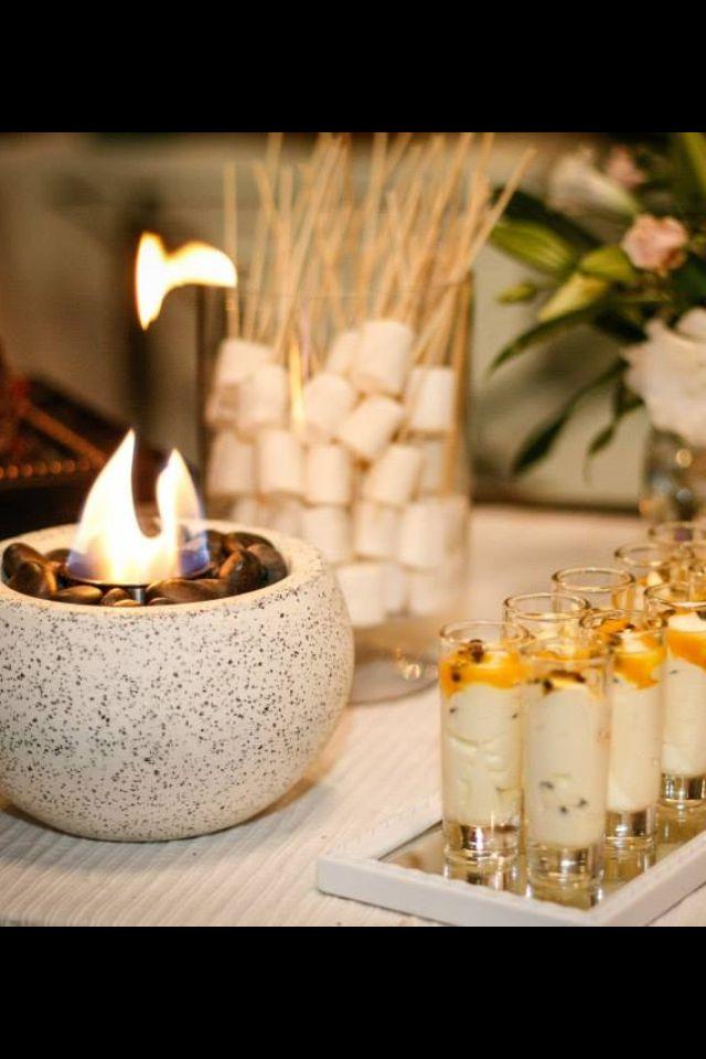 Linda idea de mini fogón de mesa para asar marshmallows y linda presentación de postre de maracuya en vasos de shot cilíndricos