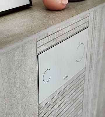 På det skandinaviske badeværelse i Ballerup falder trykket til toilettet i et med de naturlige fliser. Her i gråt glas fra Viega